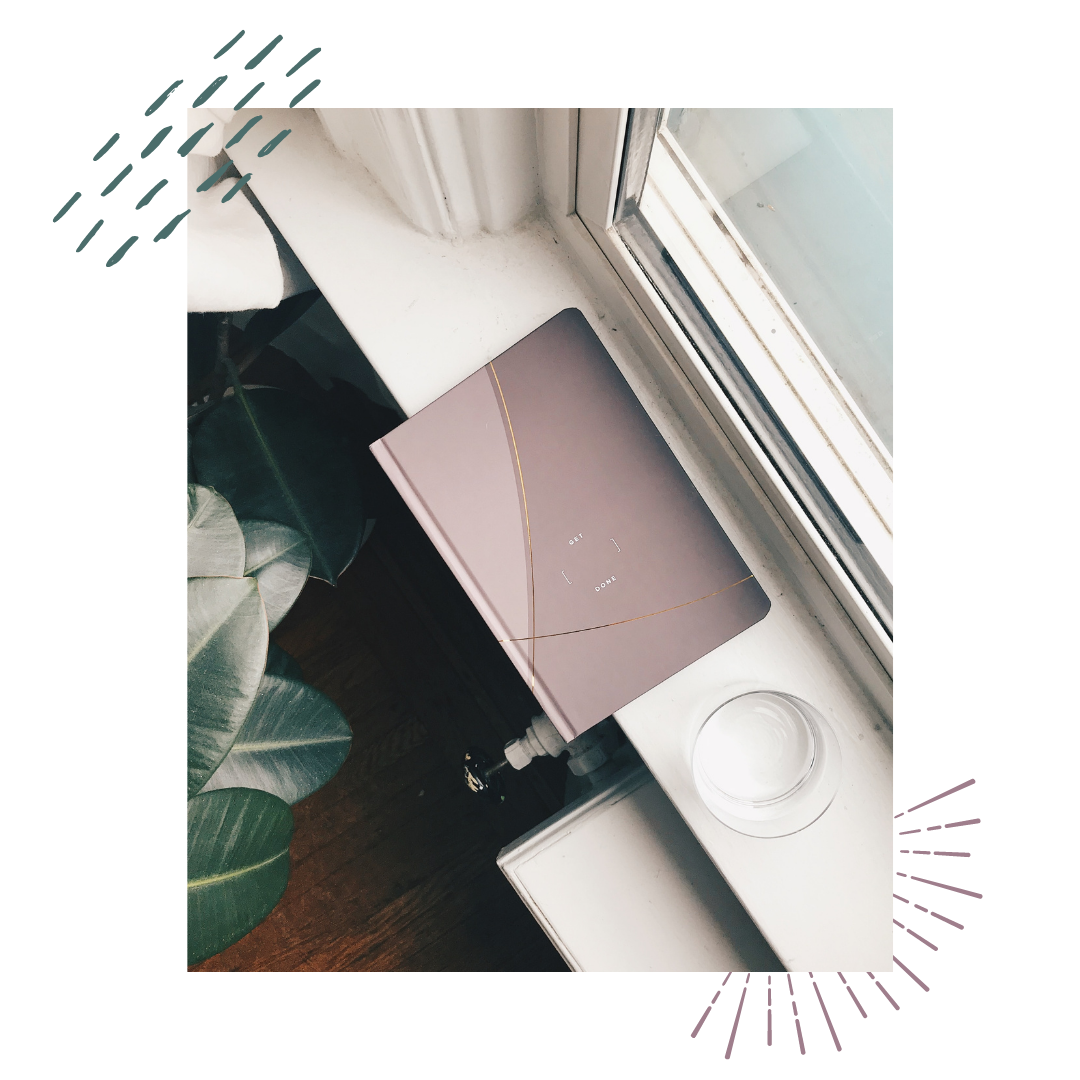 a pink journal on a shelf with a glass of water near a plant by a window